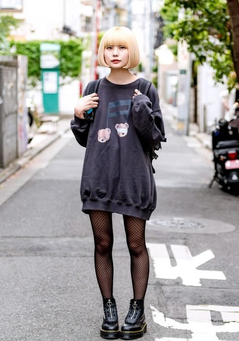 Moda japonesa harajuku; chica rubia con corte de hongo, con suéter oversized, medias de red y botas negras de plataforma