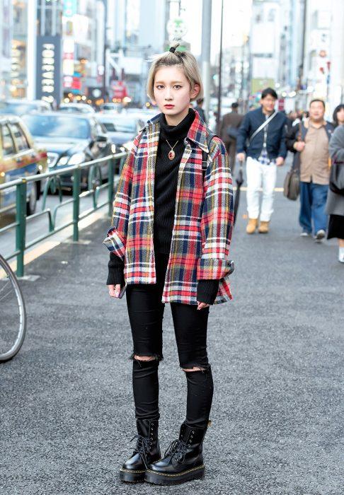 Moda japonesa harajuku; chica con estilo grunge, pantalones negros entubados, botas negras de trabajo y camisa de cuadros