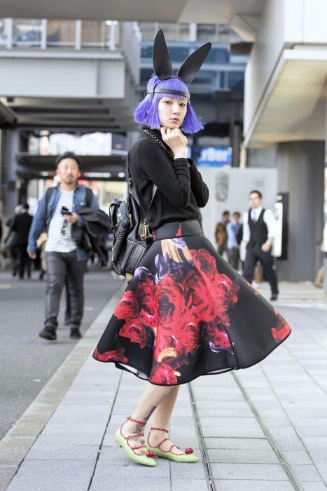 Moda japonesa harajuku; chica de cabello corto color morado, con orejas de conejo, suéter negro y falda floreada