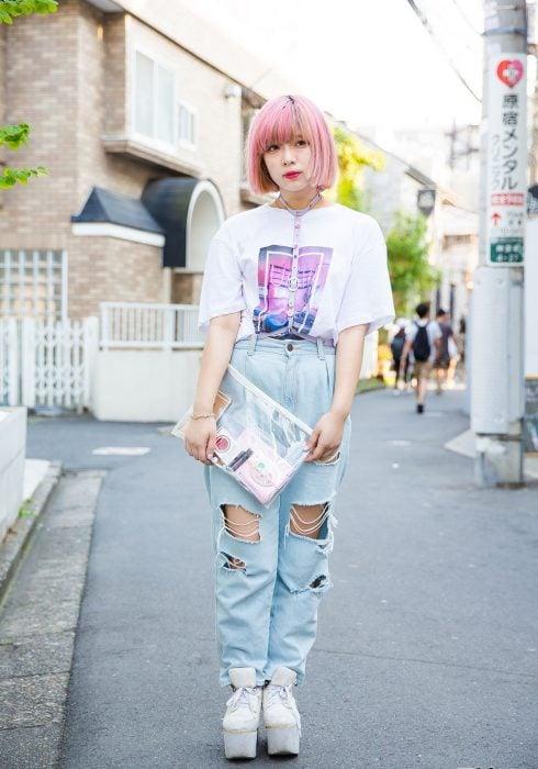 Moda japonesa harajuku; chica de cabello corto y rosa, con playera oversized, mom jeans desgastados, bolsa transparente, arnés y zapatos de plataforma