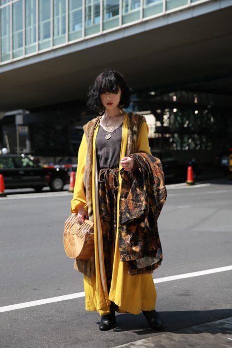 Moda japonesa harajuku; mujer con ropa en capas, gabardina amarilla y bolsa de madera