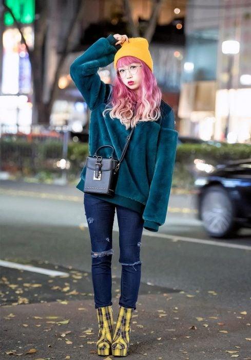 Moda japonesa harajuku; chica de cabello rosa, con gorro amarillo, suéter holgado verde de terciopelo, pantalones ajustados y botas amarillas de cuadros