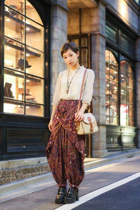 Moda japonesa harajuku; mujer de cabello lacio con corte pixie, blusa de gasa y pantalones holgados
