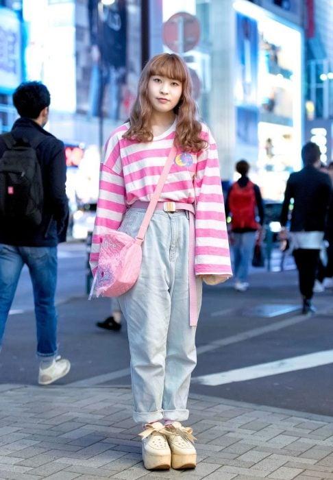 Moda japonesa harajuku; chica de cabello castaño con fleco, suéter holgado de rayas rosas, mom jeans y zapatos de plataforma