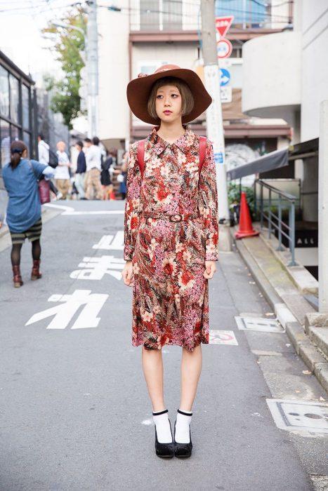 Moda japonesa harajuku; chica en la calle con vestido floral vintage, sombrero de verano y zapatos con calcetas blancas
