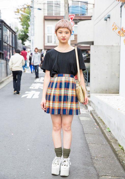 Moda japonesa harajuku; chica de cabello color rosa con corte pixie, posando en la calle con blusa negra básica y falda de tablas con patrón de cuadros con zapatos de plataforma
