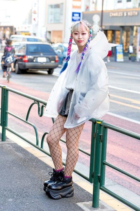 Moda japonesa harajuku; chica con peinado de trenzas de colores, chamarra transparente de plástico, short con medias y tenis de plataforma