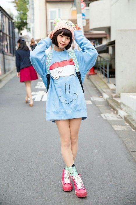 Moda japonesa harajuku; chica posando para foto en la calle, con suéter holgado kawaii de sushi y gorro tejido