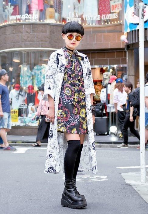 Moda japonesa harajuku; mujer de cabello corto, con lentes redondos tornasol, vestido floral y kimono con estampado de dinujos, zapatos de plataforma con calcetas
