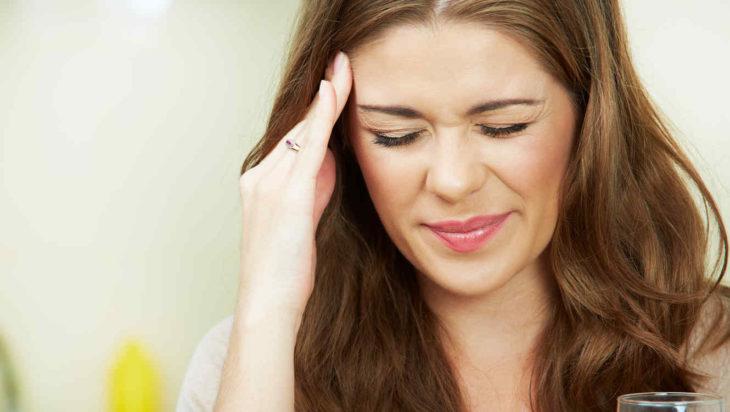Mujer agarrándose la cabeza porque tiene migraña