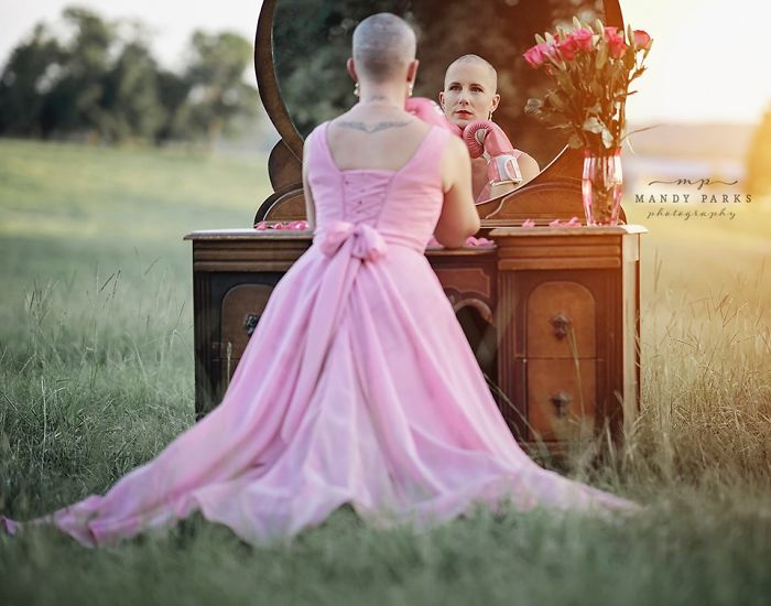 Kelsey Johnson usando guantes para boxear en color rosa, mirándose al espejo