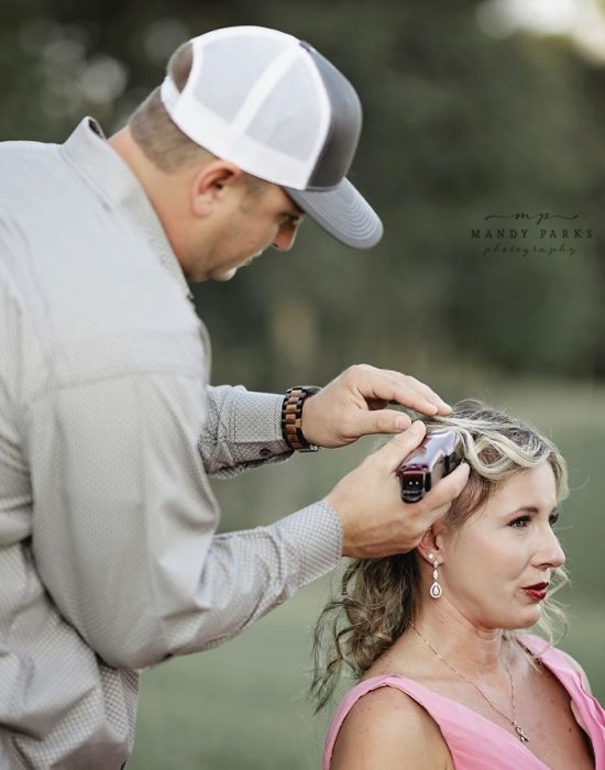 Charlie cortando el cabello de su esposa Kelsey Johnson con una maquina para rasurar