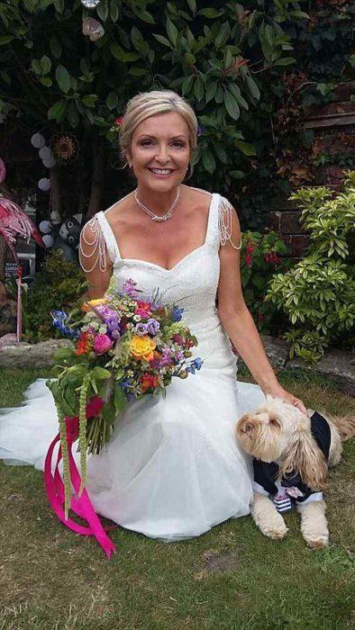 Mujer usando un vestido de boda blanco mientras posa para una sesión de fotos acompañada de su perro