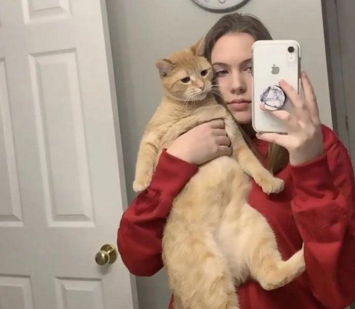 Chica cargando a su gato mientras se toman una divertida selfie en el baño
