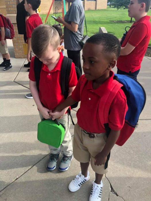 Niño tomando la mano de su compañero que acaba de entrar a clases