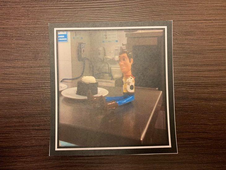 Fotografía sobre una mesa de madre con Woody comiendo pastel