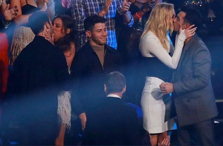 Nick Jonas en medio de sus hermanos mientras ellos besan a sus esposas