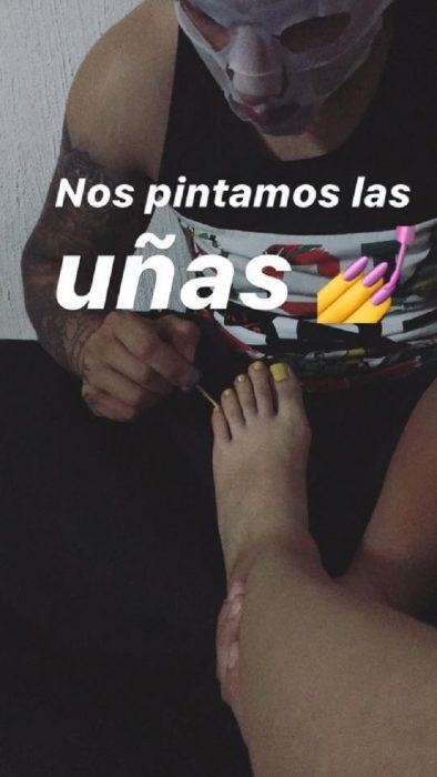 Novio planea noche de chicas con su novia; hombre pintándole las uñas de los pies a su pareja
