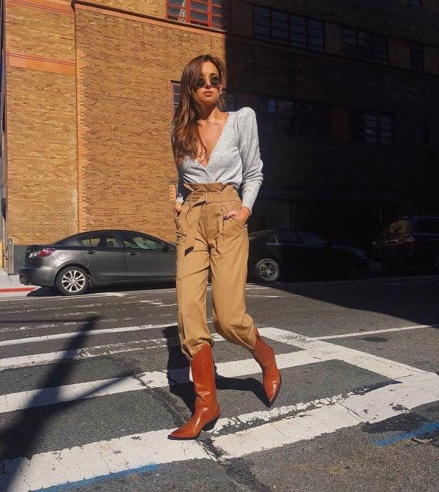 Chica usando un atuendo de color neutro con botas vaqueras de color café mientras camina por la calle