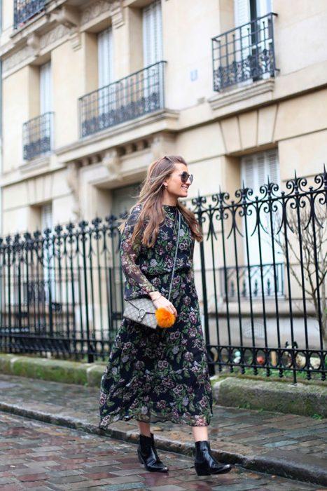 Chica usando un vestido de estampado floral con botas vaqueras