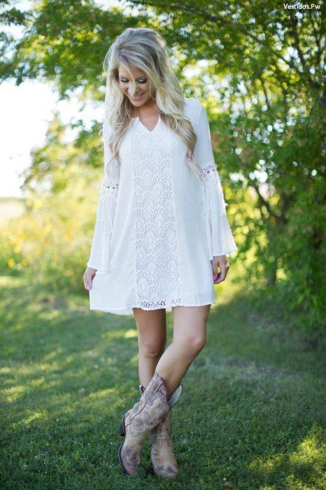 Chica usando un vestido de color blanco con botas vaqueras de color café