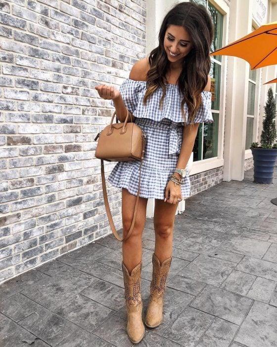 Chica usando un atuendo de vestido con botas vaqueras