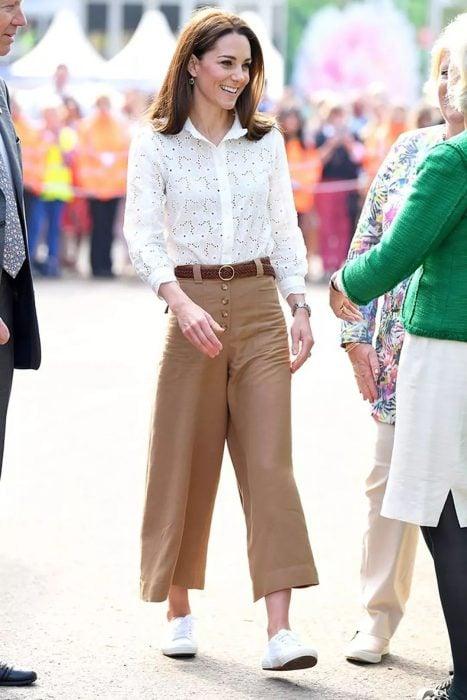 Kate Middleton usando unos pantalones culottes de color café, blusa blanca y tenis de color blanco