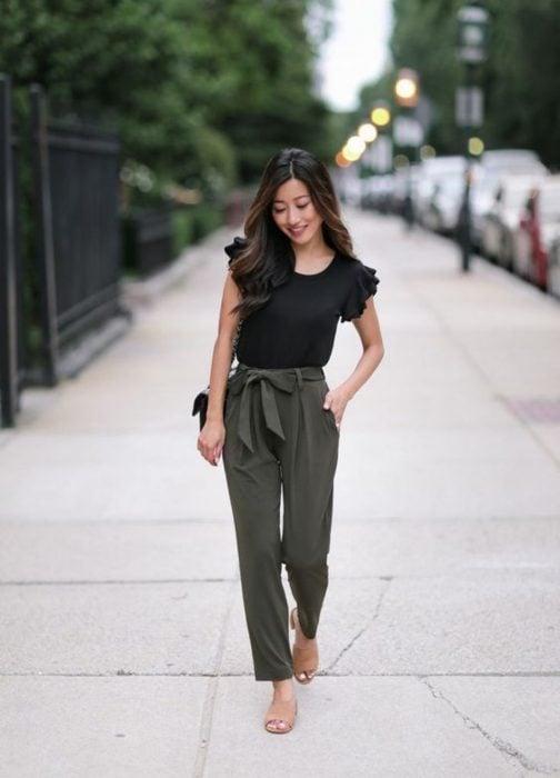 Chica usando un pantalón verde miliar, blusa negra y sandalias de tacón cuadrado bajas