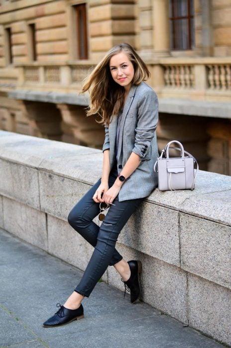 Chica sentada mientras usa unos jeans, blazer y zapatos bajos de color negro