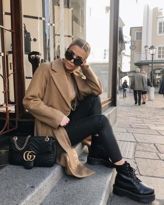 Chica sentada en unas escaleras usando una chaqueta de color camel, outfit de color negro y botas dr. Marteens