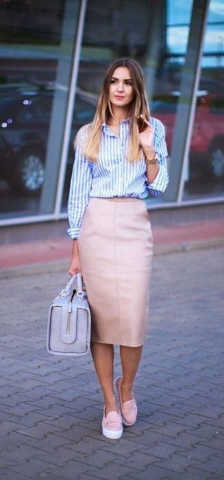 Chica usando una falda de lápiz en color rosa, blusa de botones en color azul y tenis de color rosa