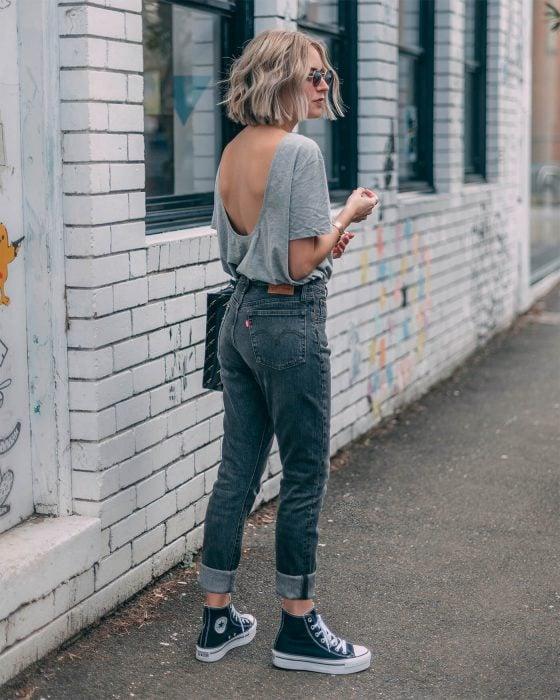Chica usando jeans con converse y blusa de escote en la espalda de color gris
