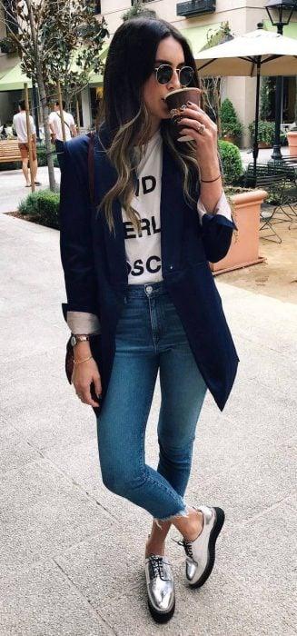 Chica usando un blazer negro, jeans y zapatos plateados