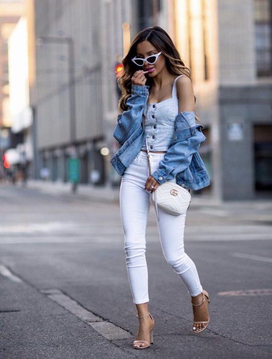 Chica usando un conjunto de color blanco con chaqueta de mezclilla y sandalias