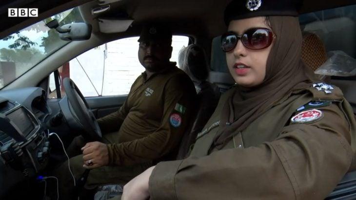 Kulsoon Fátima en un vehículo de la policía con su compañero oficial