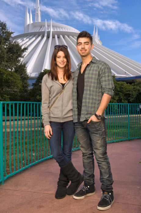 Joe Jonas y Ashley Greene posando para una foto mientras están en un parque