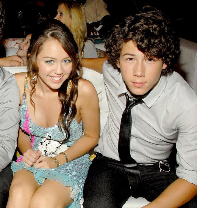 Miley Cyrus y Nick Jonas sentados y posando para una fotografía mientras están en una cena