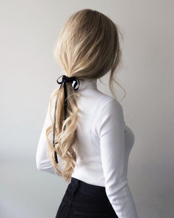 Chica con un peinado de coleta baja adornada con un moño