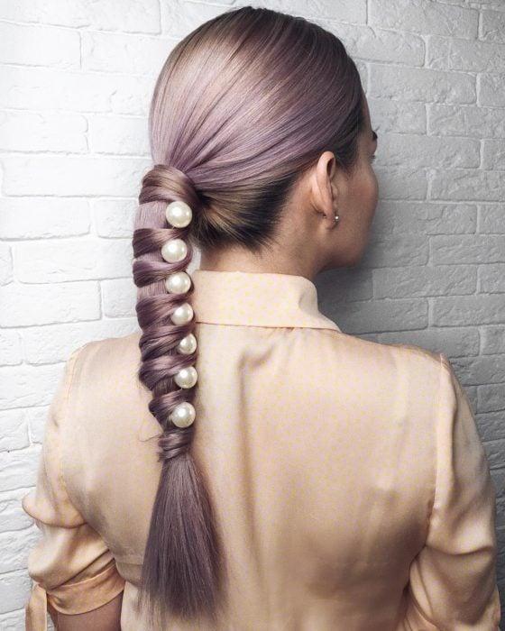 Chica con un peinado de coleta adornada con perlas