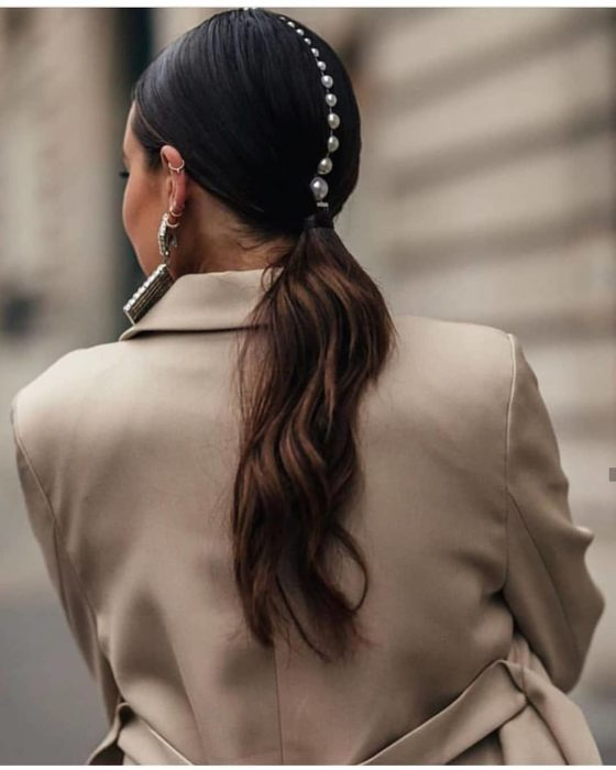 Chica con un peinado de coleta de caballo con perlas adornandola