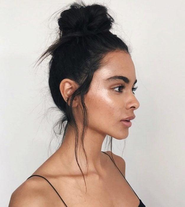 Chica con peinado bun alto desordenado con costados a los lados