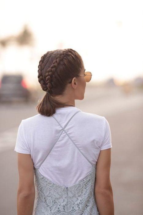 Chica de espaldas mostrando su cabello corto peinado en trenzas a los costados