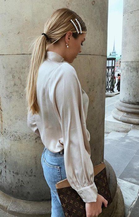 Chica con peinado de coleta baja decorado con pasadores a los costados