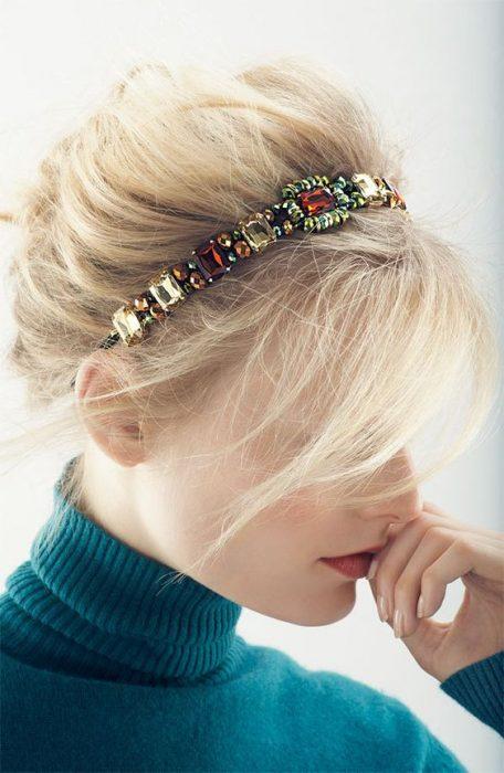 Chica de perfil cubriendo su rostro con su cabello peinado en bun desordenado decorado con una diadema de piedras