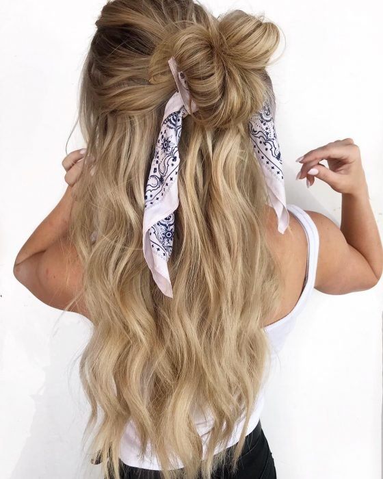 Chica de espaldas mostrando su cabello recogido con moño alto despeinado y decorado con una bandanna