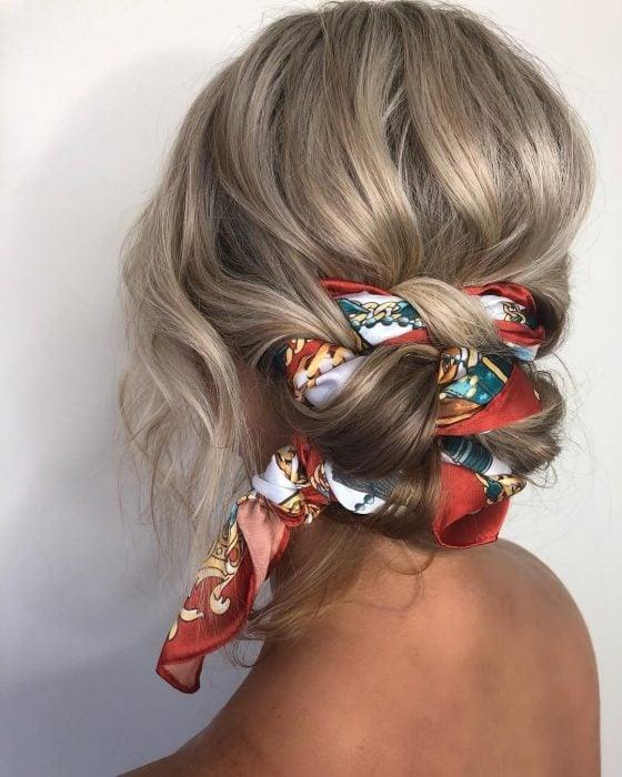 Chica con peinado bun bajo decorado con un paliacate de colores