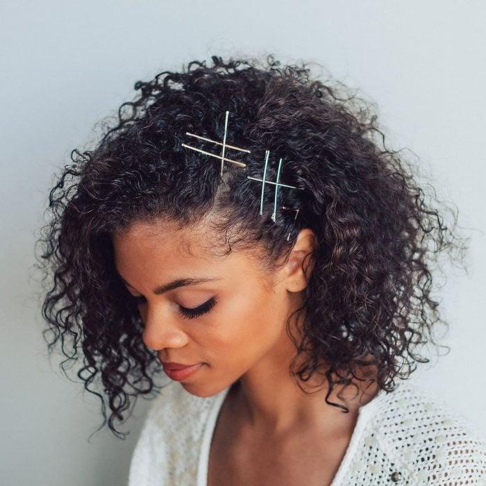 Chica de cabello rizado peinado con pasadores a los costados