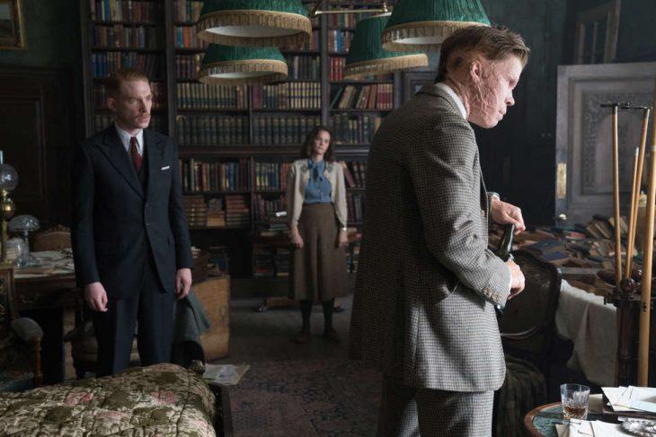 Pareja dentro de una habitación de biblioteca, escena de la película The Little Stranger
