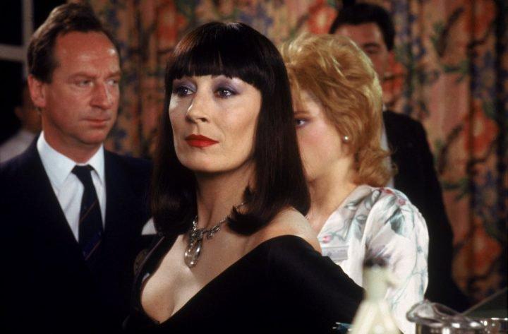 Angelica Huston sentada en una selli en un gran sal+on, escena de la película La maldición de las brujas