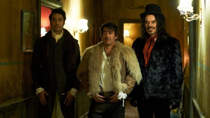 Grupo de hombres con aspecto vampiresco en el pasillo de un hotel. escena de la película What We Do in the Shadows